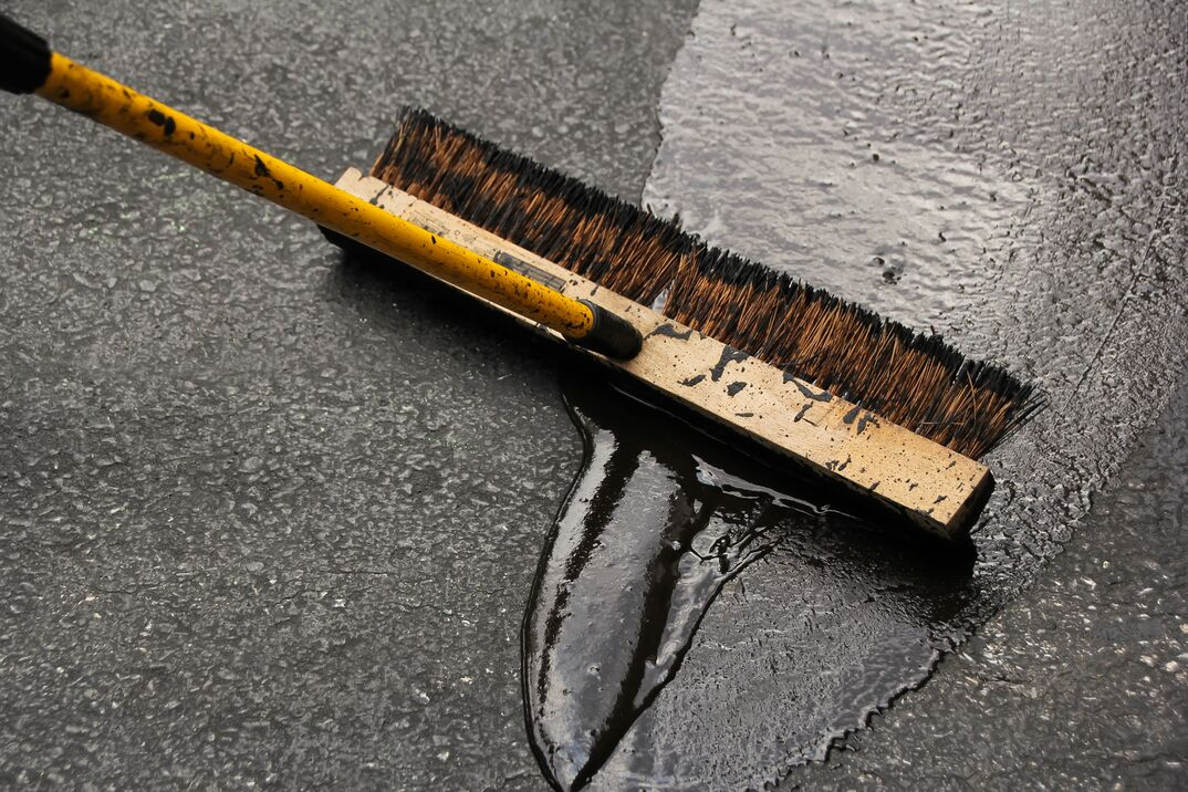 Broom being used to seal blacktop Asphalt Driveway