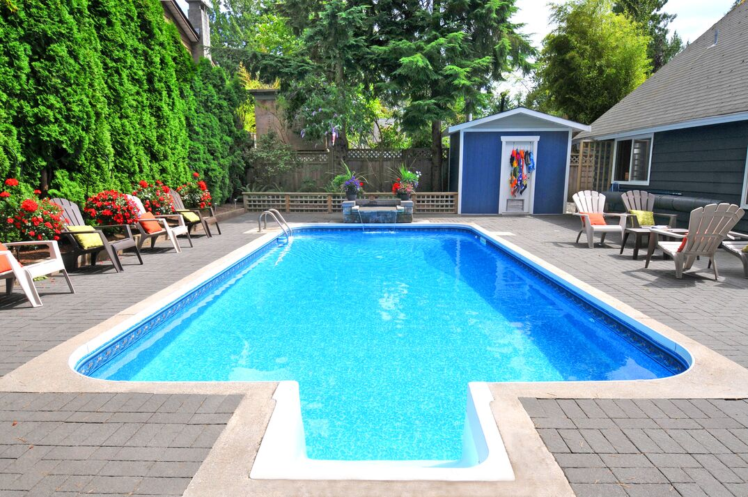 concrete and stone in-ground pool in well landscaped back yard