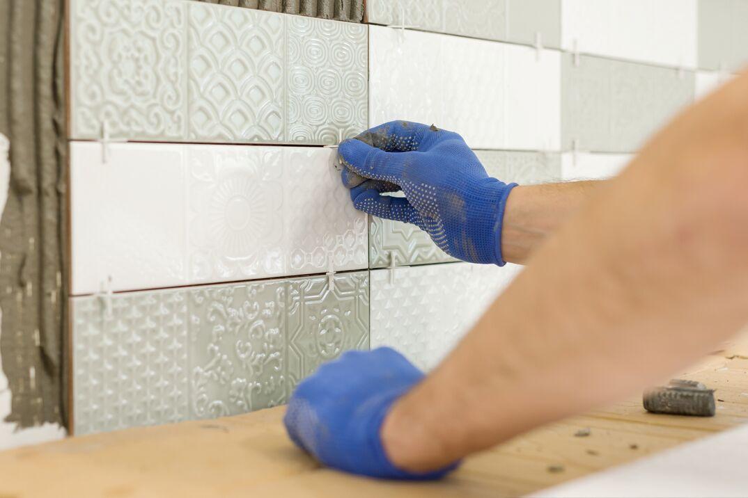 Placing tile spacers with hands on a kitchen backsplash being installed