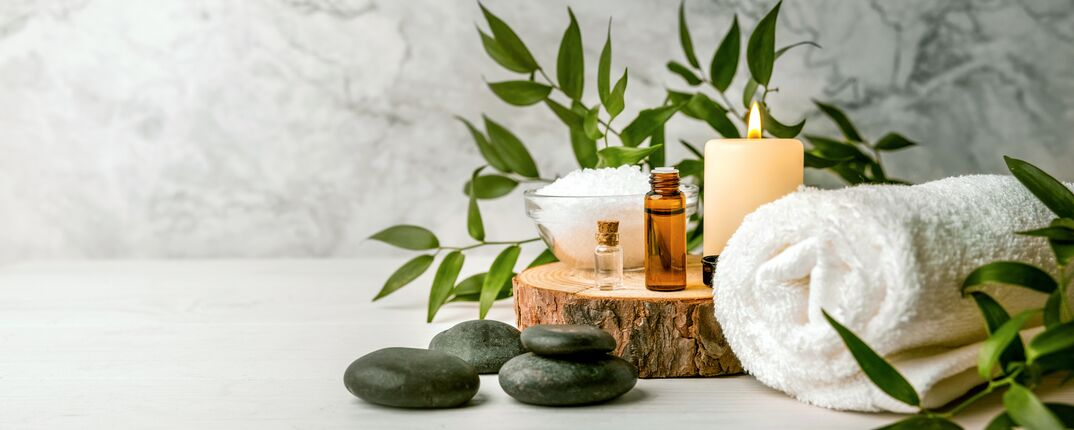 beauty treatment items for spa procedures on white wooden table  massage stones, essential oils and sea salt  copy space