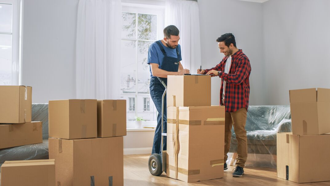 Happy New Homeowner Welcomes Professional Mover with Hand Truck full of Cardboard Boxes, Receives His Goods and Signs on Clipboard