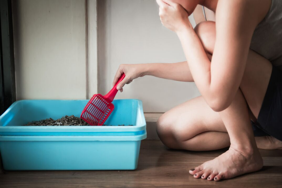 woman kneeling next to a blue litter box  with a pink scoop and plugging her nose