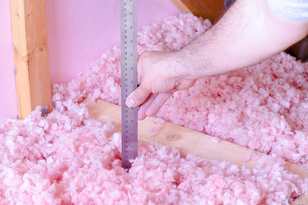 man is checking the energy efficiency of their house by measuring the thickness of fiberglass insulation in the attic