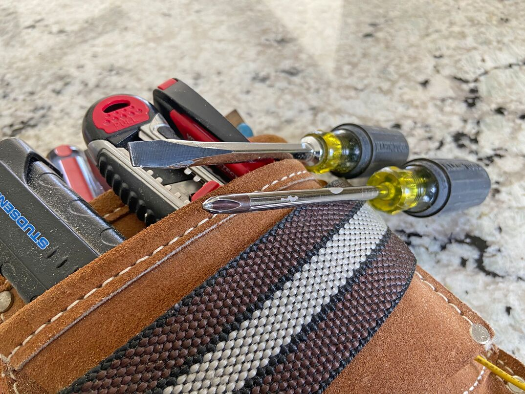 a set of Klein screwdrivers sits atop a leather tool pouch