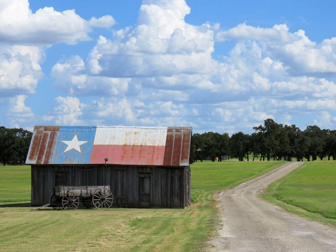 barn   buckboard wagon by rural road in Texas