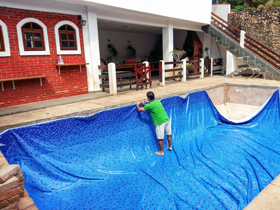 Man installing new pool liner on a concrete inground pool