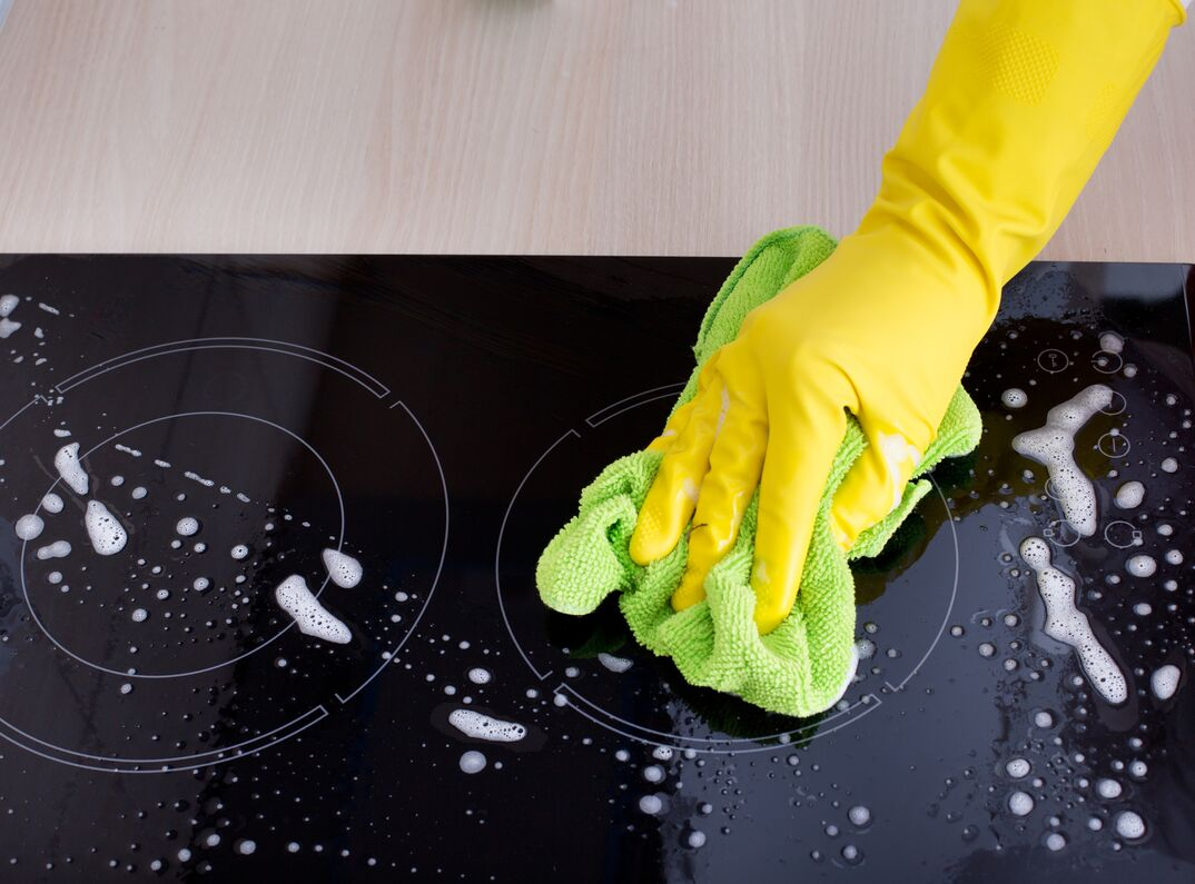 Close up of a hand with yellow protective gloves cleaning induction cooktop with green microfiber cloth