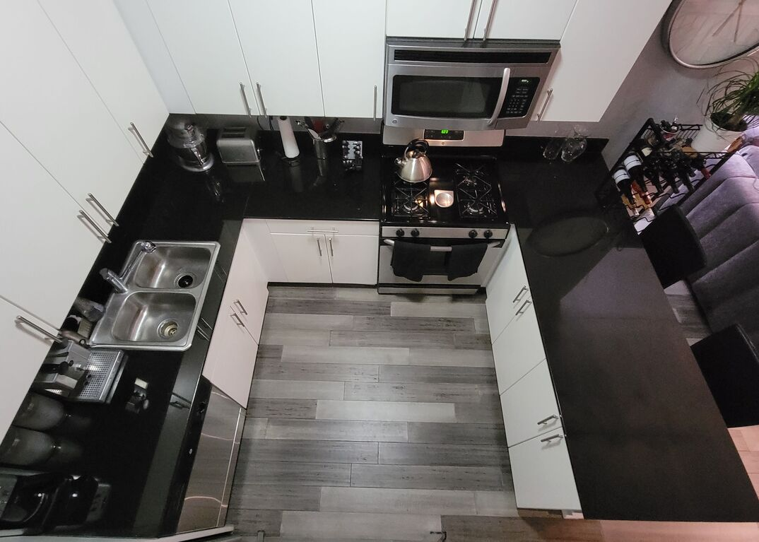 Overhead view of a modern kitchen with white cabinets, black granite countertops, gray hardwood floors and stainless steel appliances with an open floorpan leading to a living room with a wine rack and a gray couch.