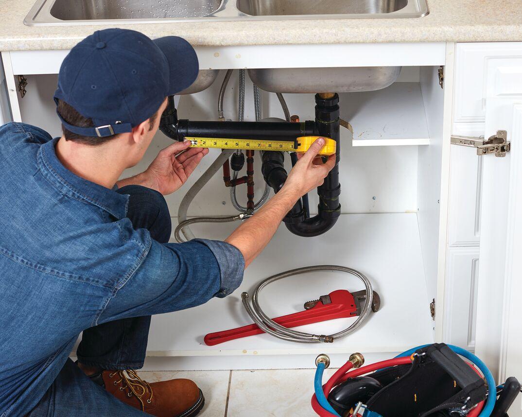 plumber fixing under sink