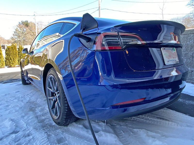 Blue 2018 Tesla Model 3 in a residential driveway getting charged