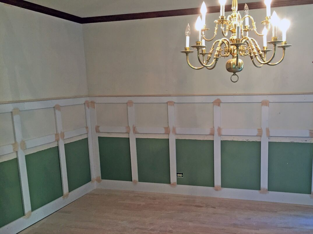 Wainscoting attached to a wall and being prepared for paint