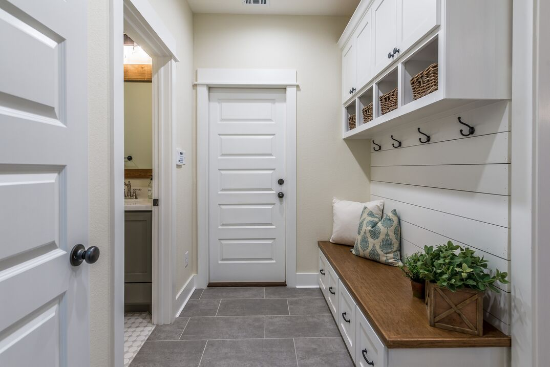 a modern white mudroom with a classif wood bench and shiplap on the wall