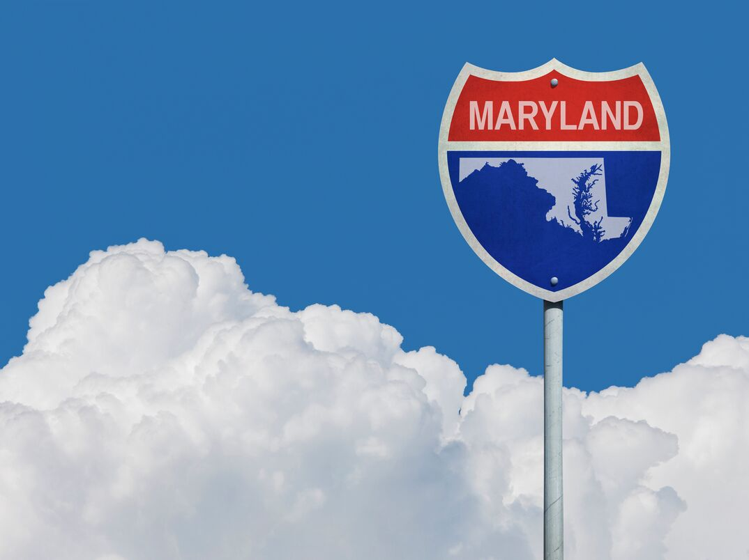 Highway sign for Interstate road in Maryland with map in front of clouds