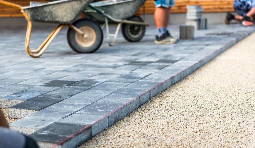 Laying gray concrete paving slabs in house courtyard driveway patio