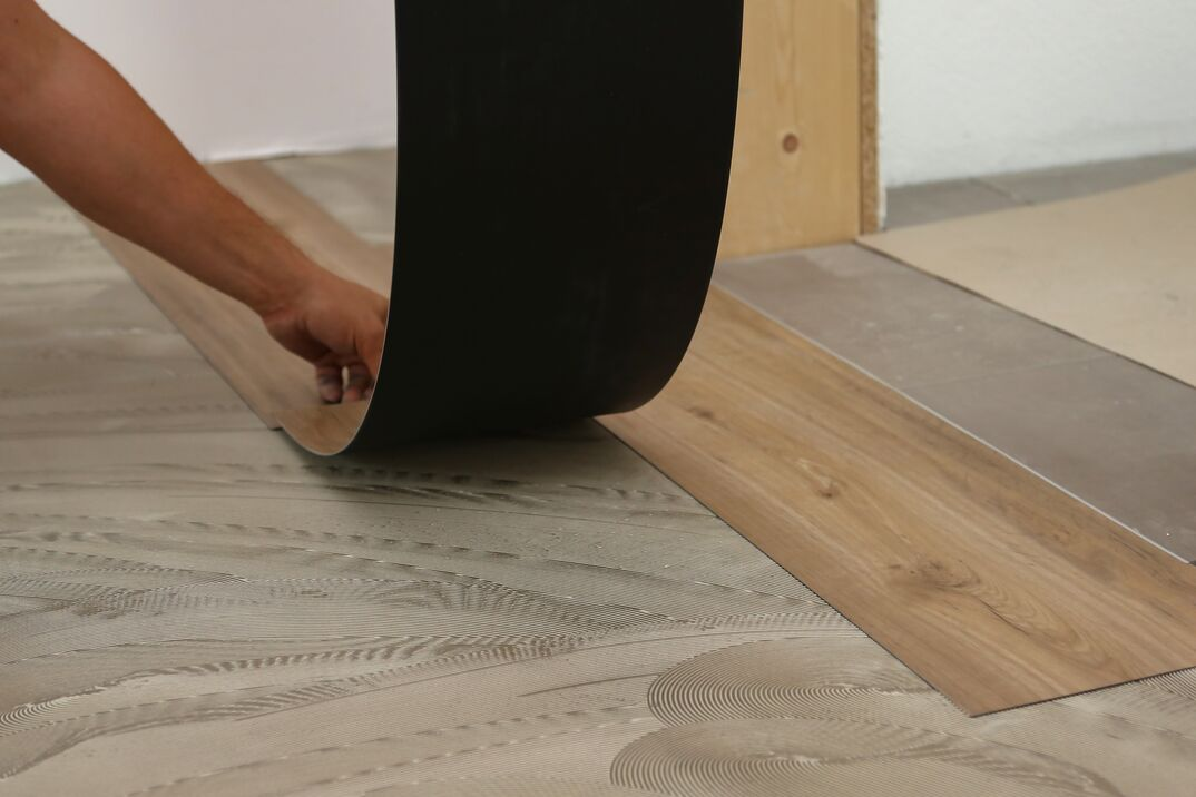 worker lays down sheets of vinyl or linoleum flooring that simulates a wood grain