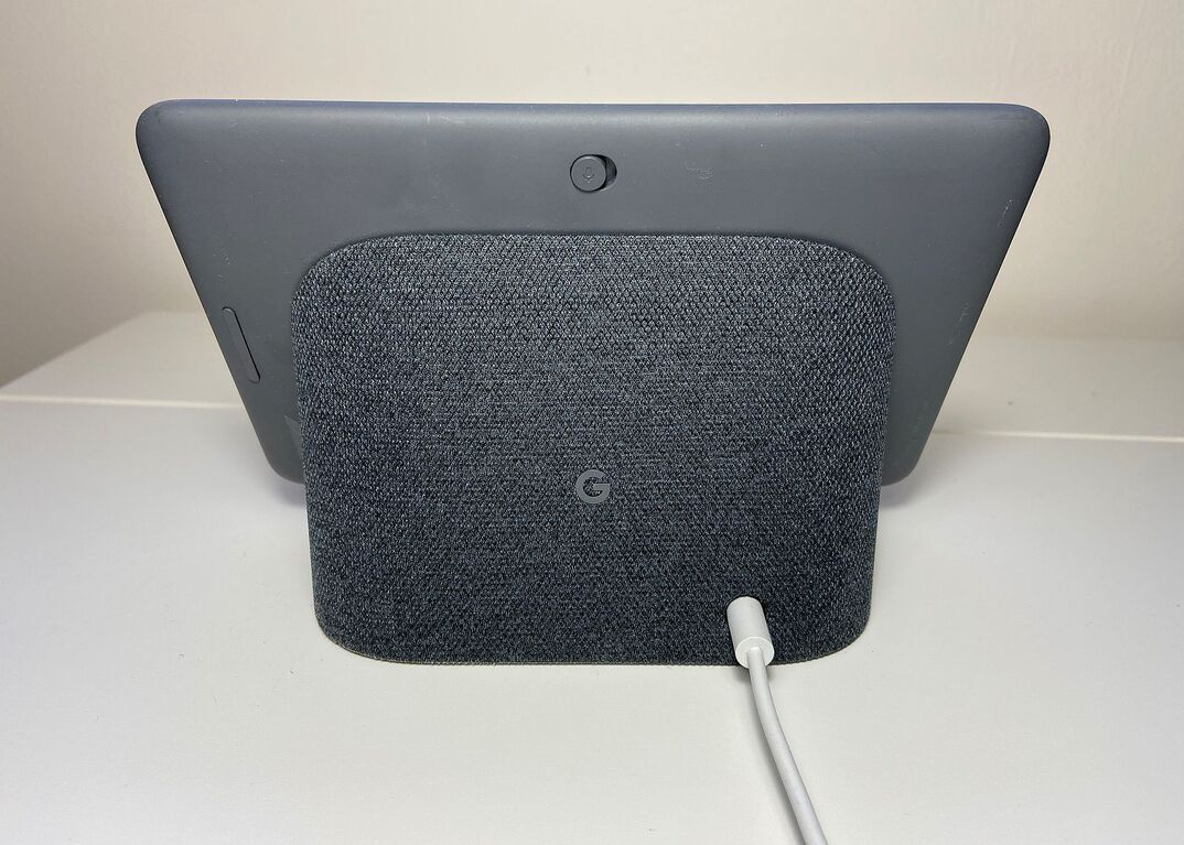 Backside view of a gray Google Nest Hub tablet resting on a white table with a cord coming out of it.