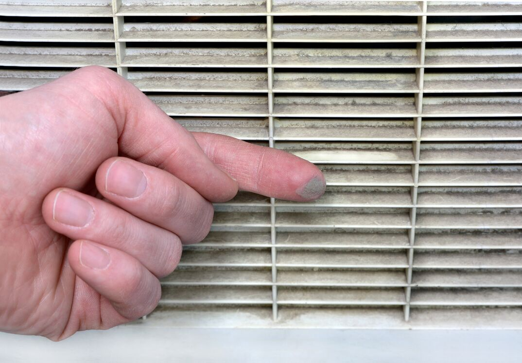 Person checks the grime of the vent grill by swiping a finger along it