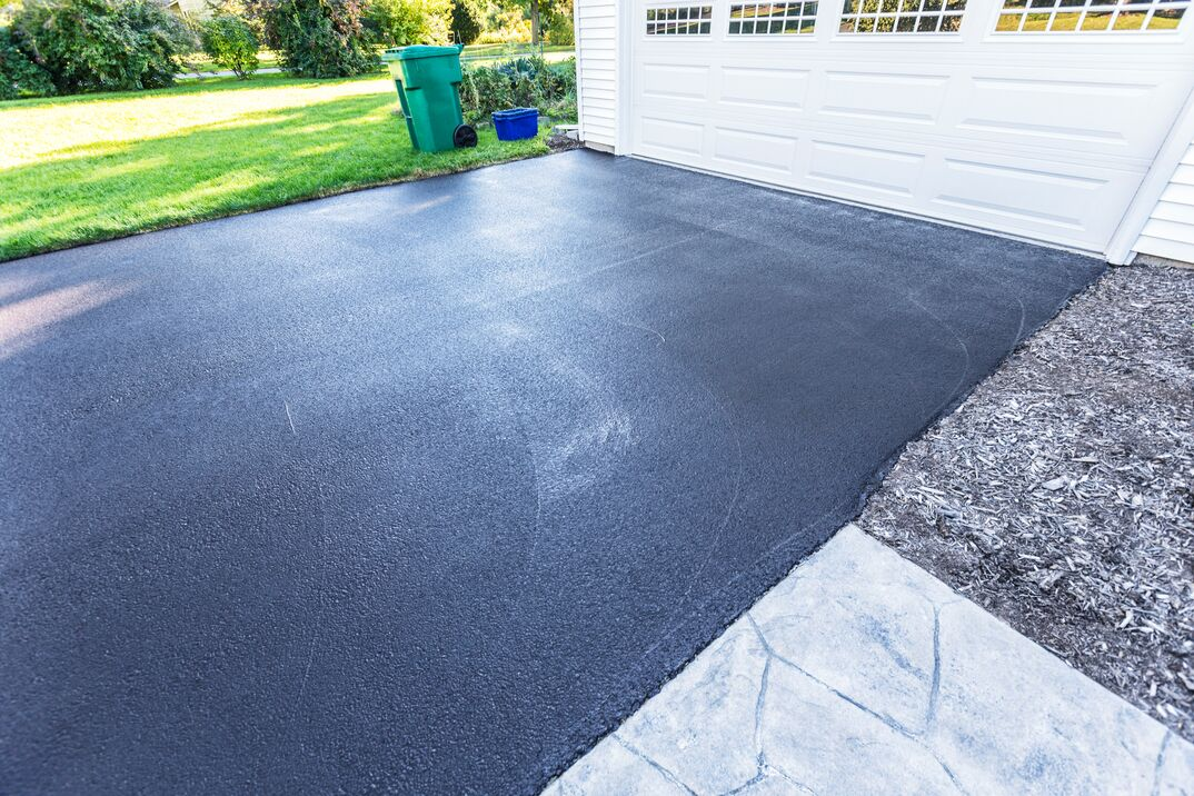 A fresh blacktop resealing job just finished on this asphalt driveway in a suburban residential