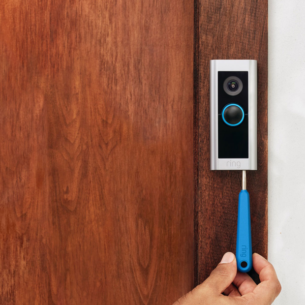 A second generation Ring video doorbell with a specialty tool being used to remove the battery