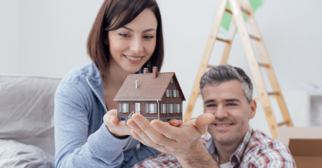 woman looking at scale model of house