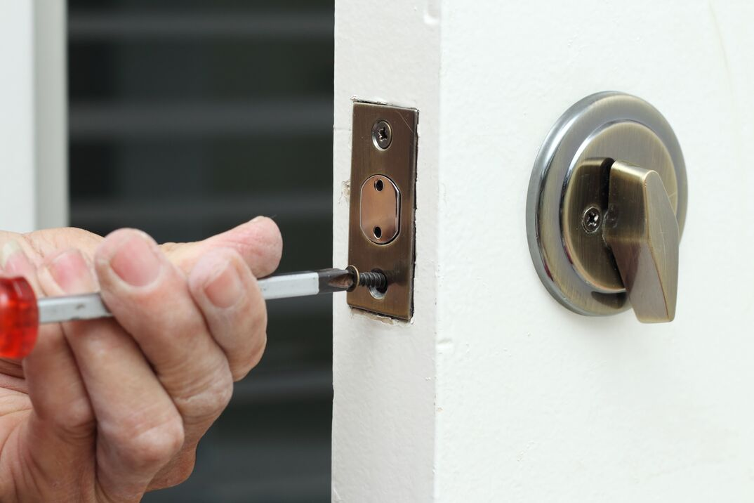 A worker is replacing the dead bolt on a home entryway door