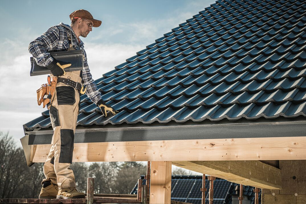 Male Worker Installing Roof Shingles
