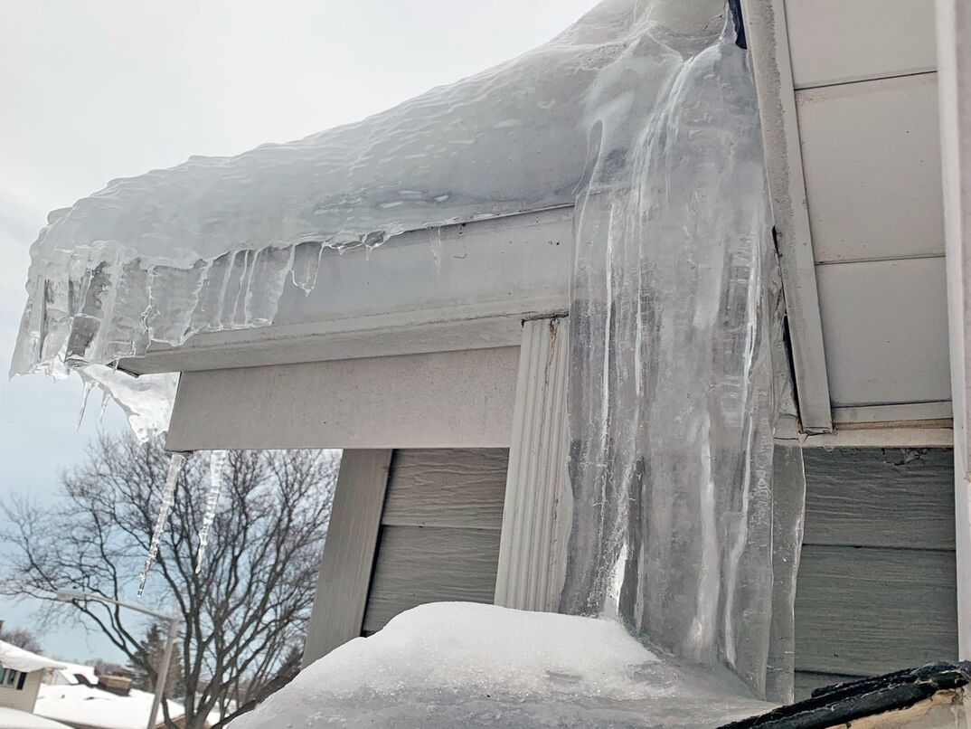 exterior of a home loaded with frozen waterfalls of ice creating a dam on the roof