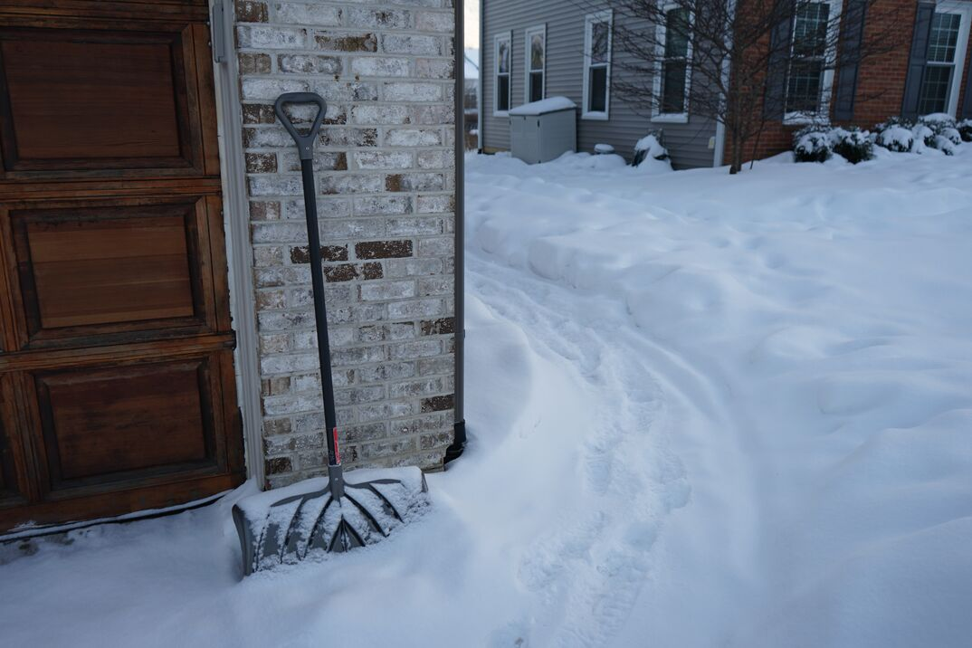 snow covered walkway and shovel