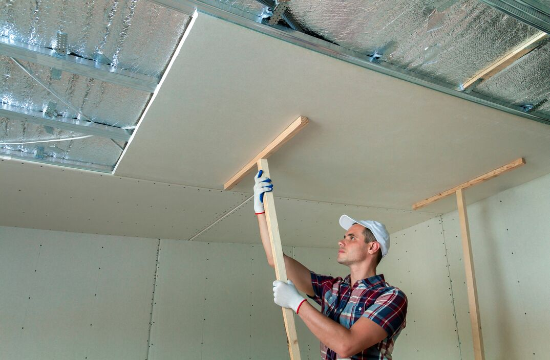 Man in protection work gloves fixing wooden holders for drywall suspended ceiling to metal frame