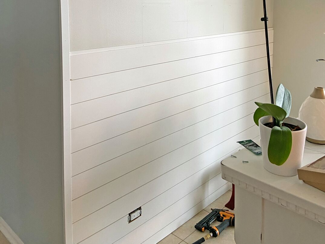a residential kitchen wall with shiplap being added  The boards go halfway up the wall to show progress  tool lay on the floor