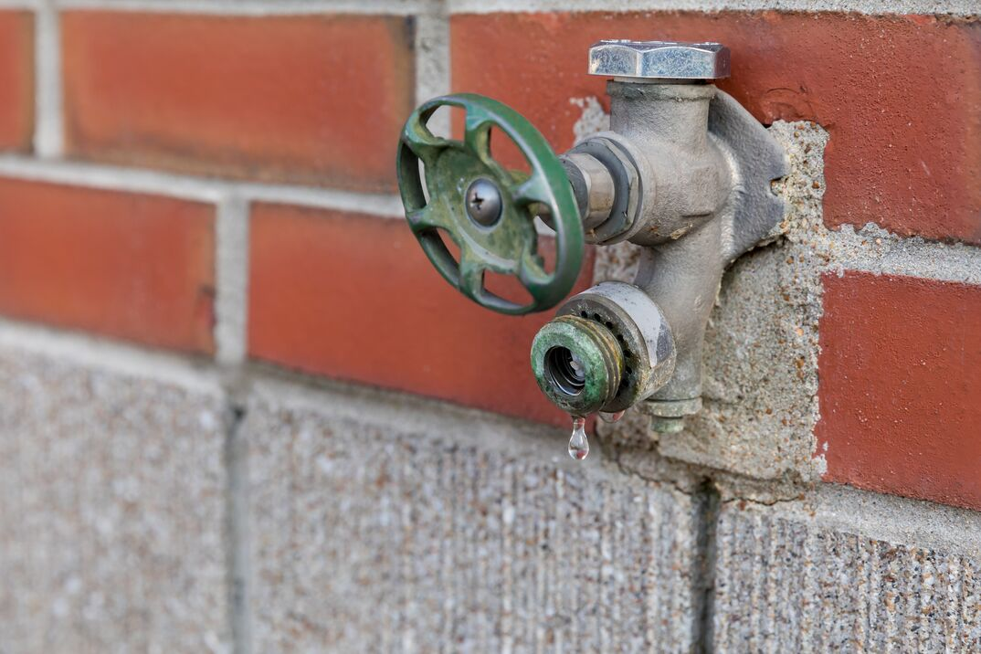 an outside house bib or faucet mounted to a home s brick exterior shown slowly leaking
