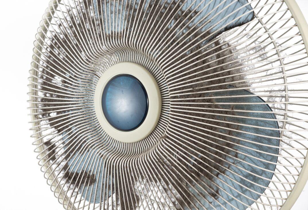 dust stuck on the fan guard of an old oscillating fan
