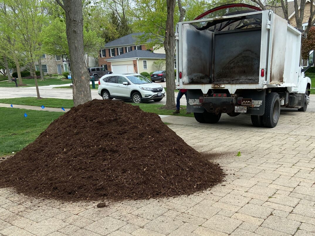 a dump truck delivering hardwood mulch on a residential driveway