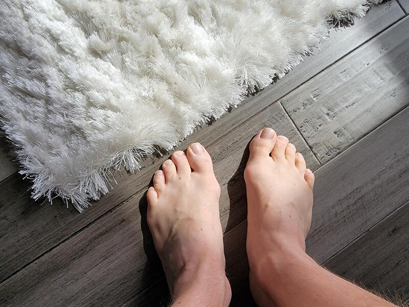 man s bare feet on the floor beside a white carpet
