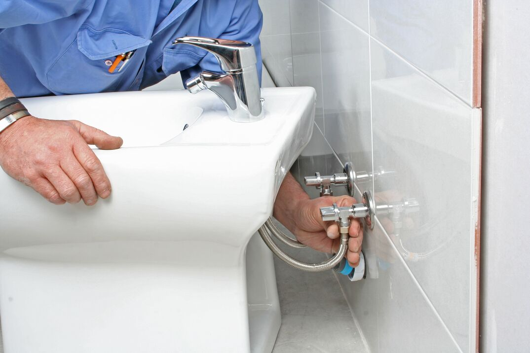 a plumber installs a bidet by connecting the water line to the fixture in the wall