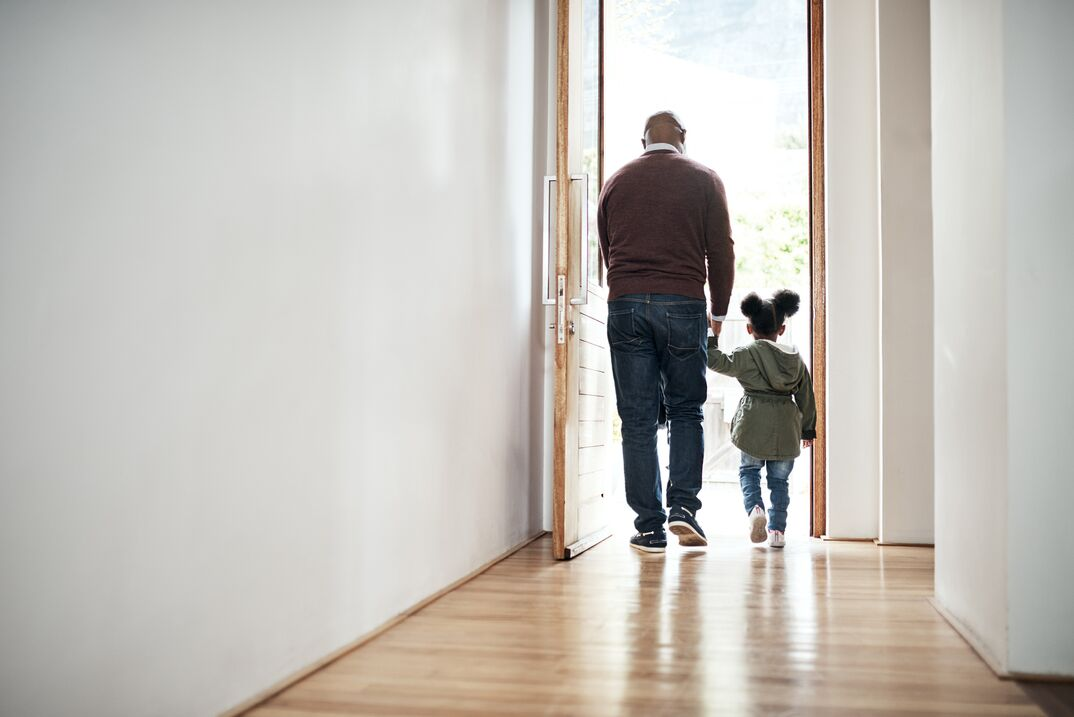 Adult man and little girl leave house through open doorway holding hands with their backs to us