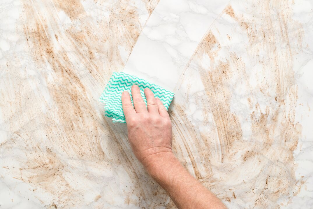 Hand Wiping Clean a Dirty Marble Surface with Paper Towel