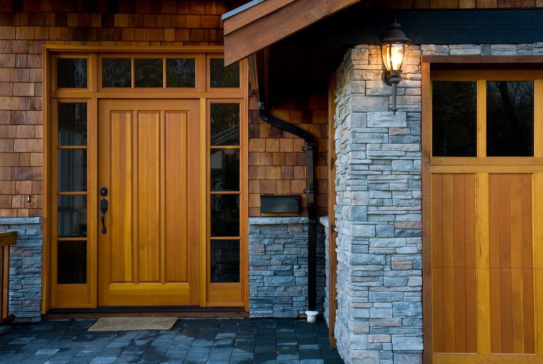 the entryway of a modern home with cedar siding and stone facade