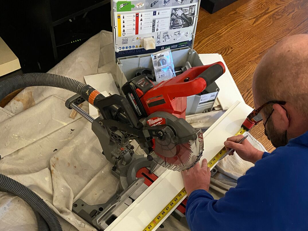 worker uses a battery-powered Milwaukee miter saw to make cuts on primed shiplap boards