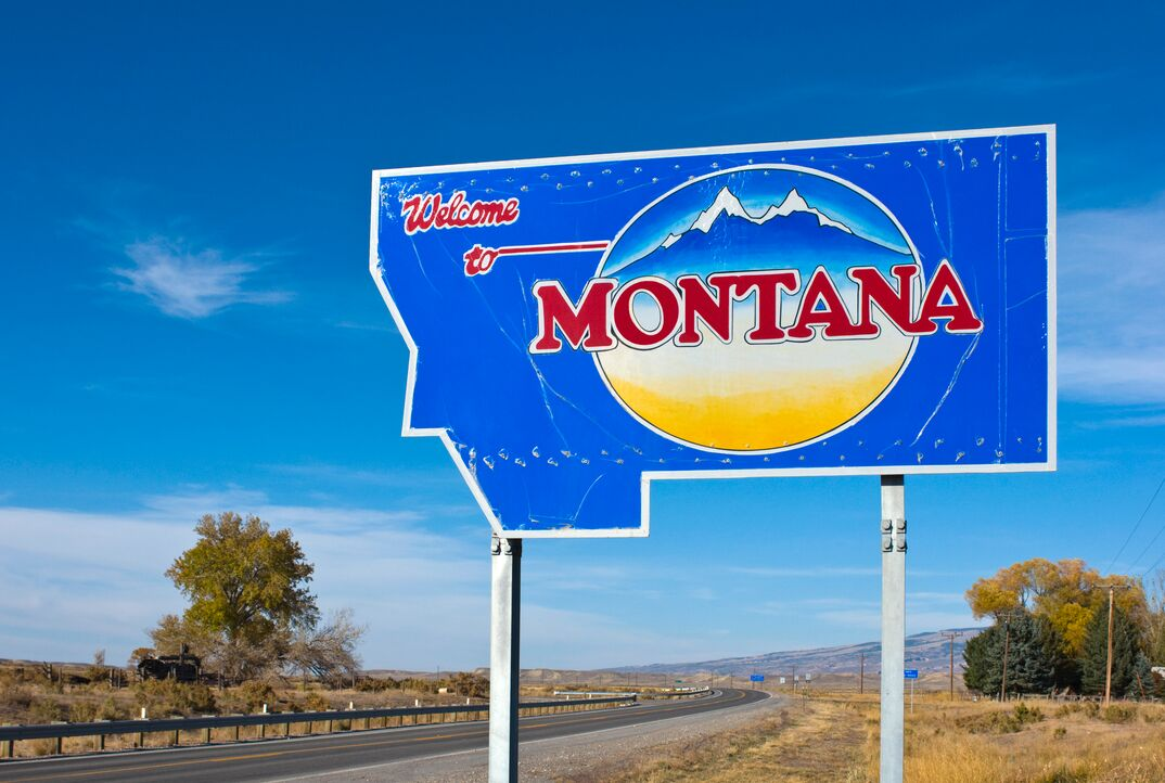 a Welcome to Montana sign sits alogside a highway