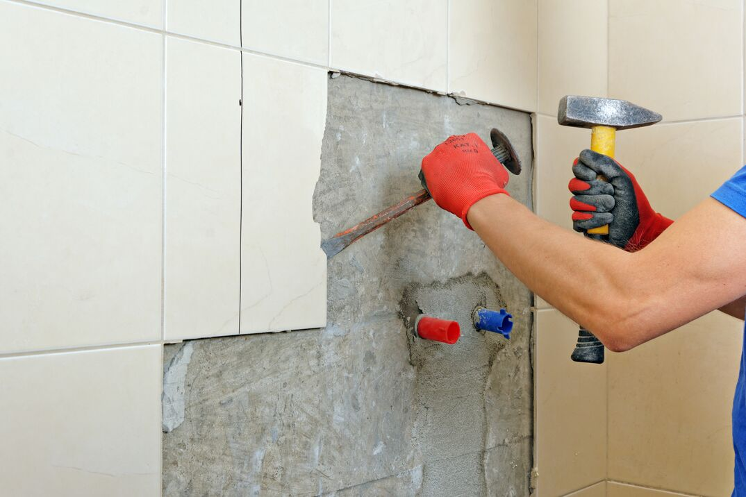 Contractor removing old tile from bathroom wall in preparation of renovation