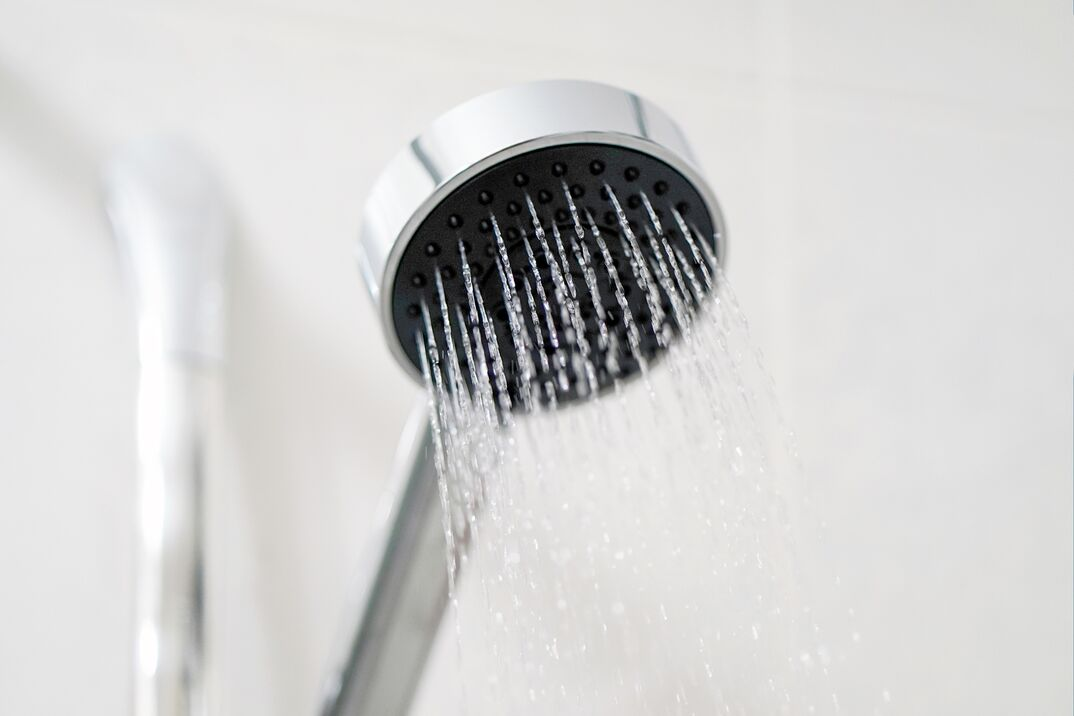 Shower head in bathroom with water spray or water flow. Fresh water flow from shower head for cleaning body.