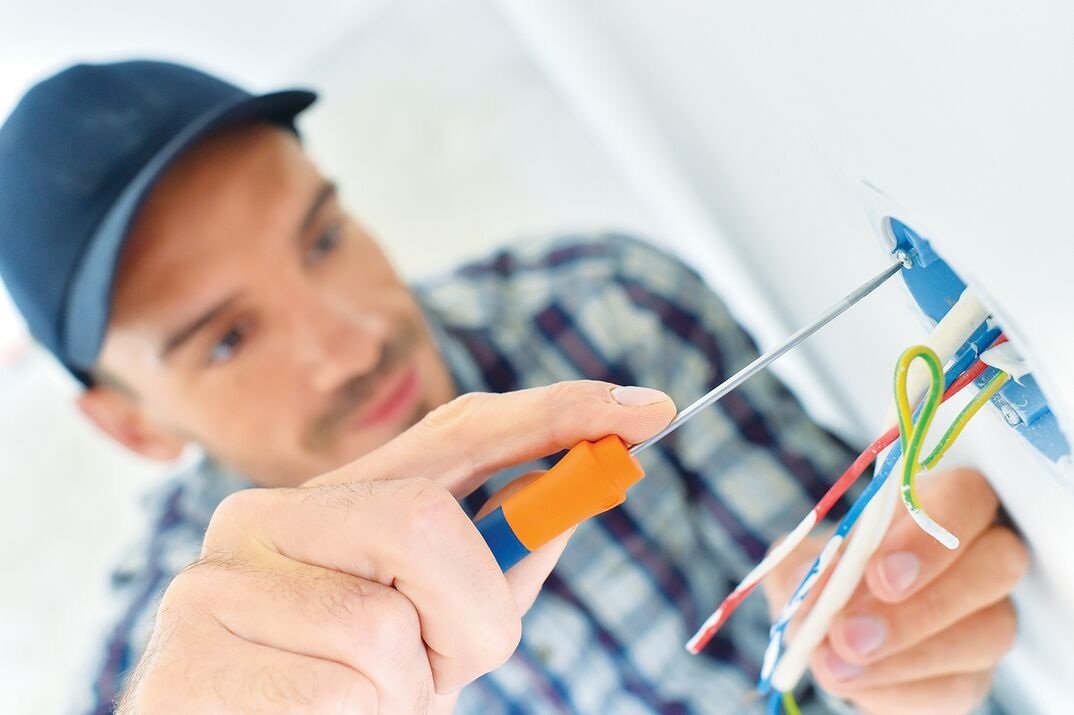 electrician fixing wall outlet with screwdriver