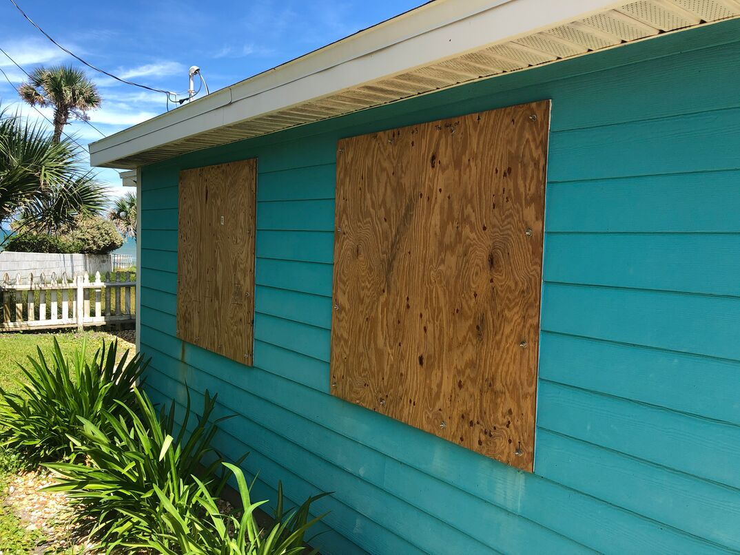 Plywood covers the windows of a beach cottage in Florida in preparation for an oncoming hurricane