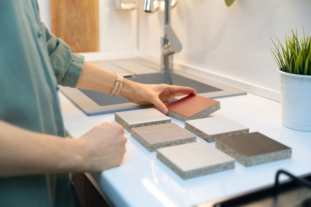 woman choosing kitchen countertop material texture from samples