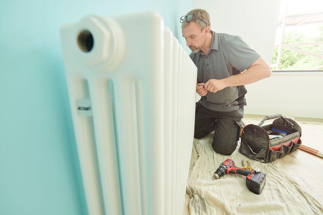 male plumber working on a residental radiator