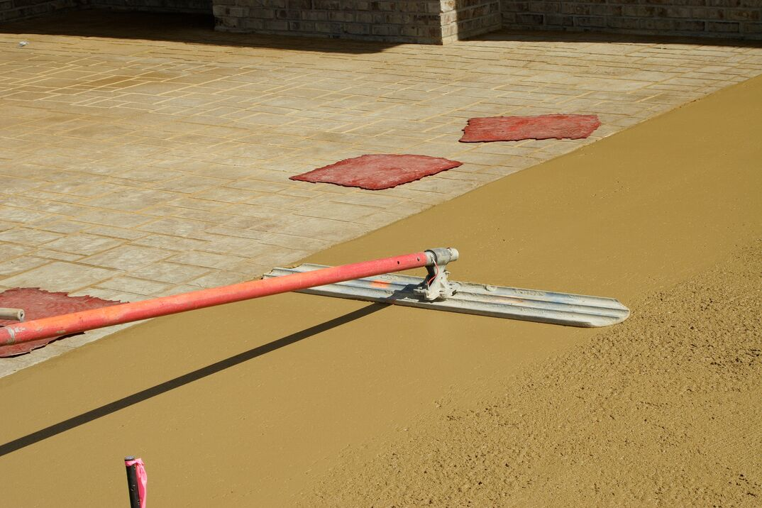 A concrete driveway gets prepped for stamping with rubber  brick  stamps laying nearby