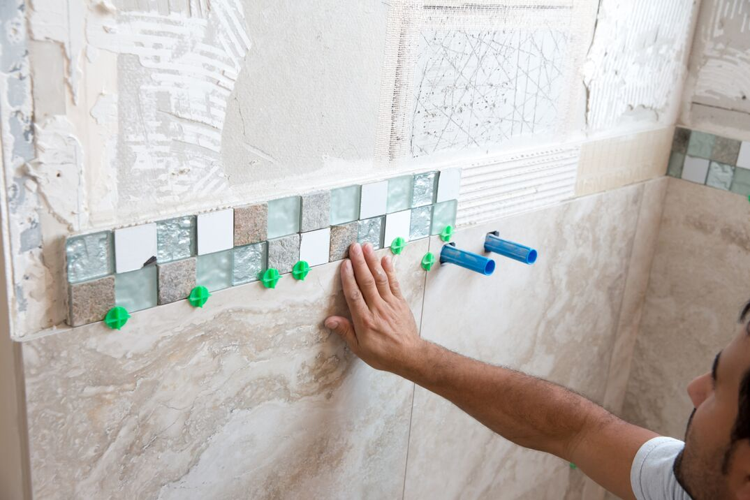 mosaic tile border made up of small square glass tiles is being adhered to a shower wall  Larger tiles are in place underneath it  The bathroom in a home The arm and head of tile worker are visible
