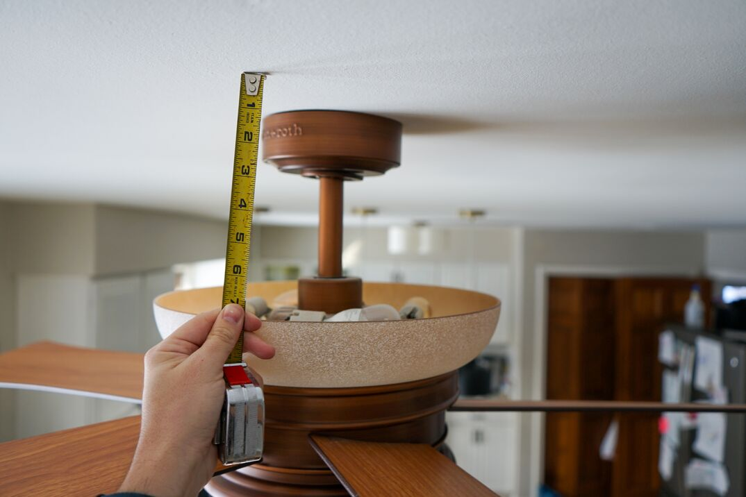 man hold a tape measure alongside a ceiling fan s downrod