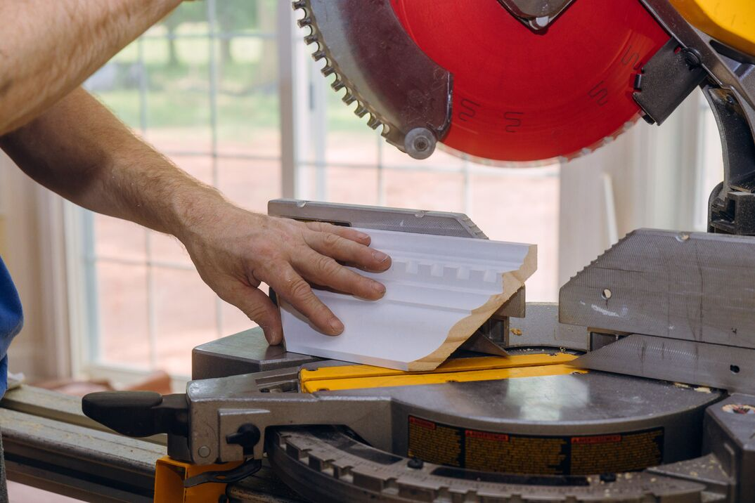 circular saw with a red blade cutting new crown moulding for renovation